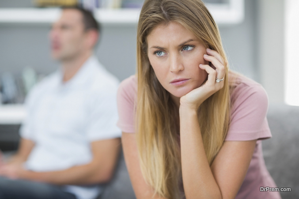 Sad woman thinking on couch after fight with husband in living room at home