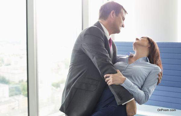 Loving business couple dancing in office