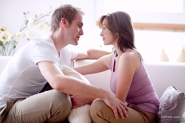 Young couple sitting on sofa, face to face