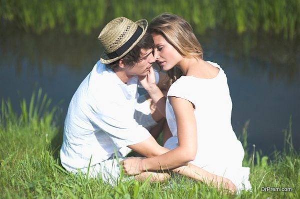 Young couple kissing on riverbank