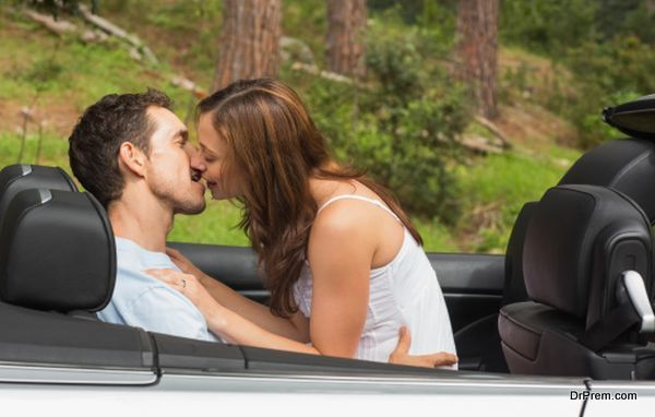 Young couple smooching on the backseat