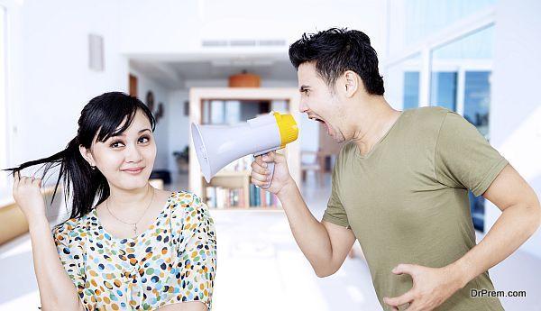 Angry boyfriend using speaker at ignorant girlfriend