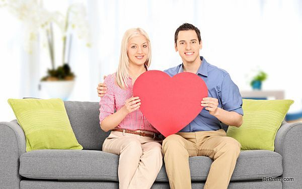 Young couple sitting at sofa and holding big red heart