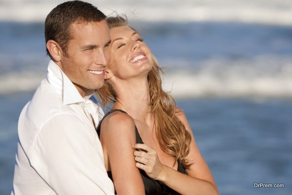 Man and Woman Couple Laughing In Romantic Embrace On Beach