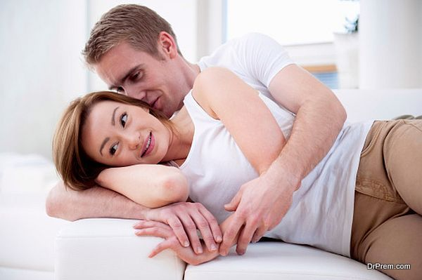 Young couple lying together on sofa